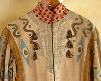 A detail of the silver panel and polka dot patterned collar on one of the robes. Gold ribbon tassels and edging add further glittering decoration against the simple background