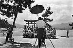 Tourists being photographed by a photographer with the background of Miyajima Torii, floating gate of Itsukushima shrine, Miyajima. It is said that Miyajima is one of the three most beautiful sites in Japan...August 4, 2002.<br />