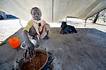 Haram Jukin, a ten-year old girl living in the Yusuf Batil refugee camp in South Sudan's Upper Nile State, prepares food in the family's shelter. More than 110,000 refugees were living in four camps in Maban County in October 2012, but officials expected more would arrive once the rainy season ended and people could cross rivers that block the routes from Sudan's Blue Nile area, where Sudanese military has been bombing civilian populations as part of its response to a local insurgency. Conditions in the camps are often grim, with outbreaks of diseases such as Hepatitis E.