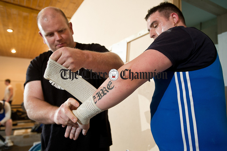 Sean Mc Namara gets his arm bandaged by trainer Gerry O Mahony during a training session at Miltown Malbay Weightlifting club. Photograph by John Kelly.