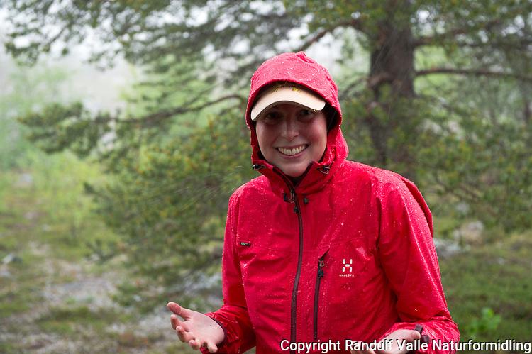 Dame med skalljakke ute i heftig regnvær. ---- Woman outside in rain.