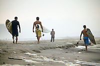 Surfer walk down Far Rockaway beach in New York, United States, in the early morning of 17 September 2005. Photo Credit: David Brabyn.