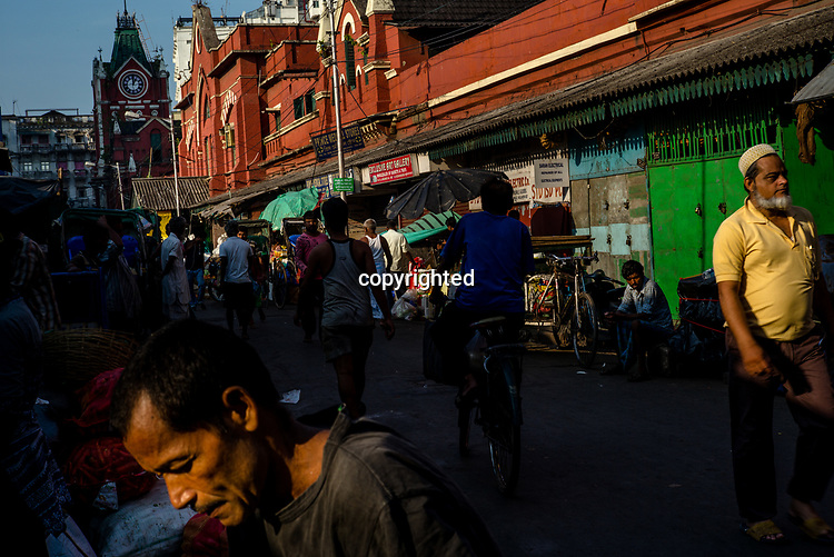 Pedestrians walk along a street in the market stall in the New Market area of Kolkata, India, on Saturday, May 27, 2017. Photographer: Sanjit Das
