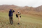 Snow Leopard (Panthera uncia) veterinarian, John Ochsenreiter, and biologist, Khalil Karimov, looking for wildlife, Pikertyk, Tien Shan Mountains, eastern Kyrgyzstan