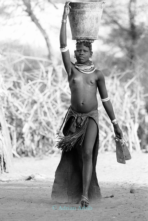 Turkana woman collecting water from a borehole and  carrying the load back to their village over 1 km away.