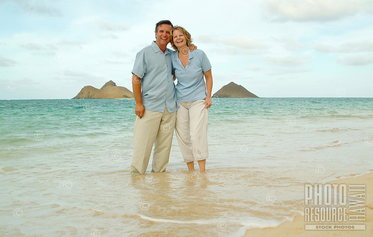 Couple in mid 50's on Lanikai beach with Moku lua islands in rear