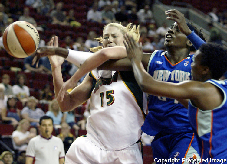 Seattle Storm's Lauren Jackson, left, has the ball knocked away by New York Liberty defenders Crystal Robinson, right, and Tari Phillips, middle, as she drives to the basket on Wednesday, July 23, 2003 in the Key Arena. The Seattle Storm beat the Liberty 75-65.  Jackson ended up leading all scorers with 27 points.(AP Photo/Jim Bryant)