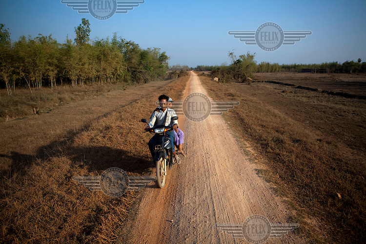 Villagers ride a motorbike on a dusty road leading to NLD leader Aung San Suu Kyi's new constituency near Wah Thi Ka.