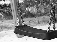 """Black & white fine art stock image of an empty swing in children's park.<br /> <br /> View the gallery - """"Conceptual- Life & Surroundings"""" for the color version of this image."""