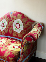 This red sofa in the living room is a design by Monica Vinader and is covered in a vibrant antique fabric