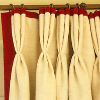 A detail of linen curtains which feature decorative pinch pleats and a contrasting red edging