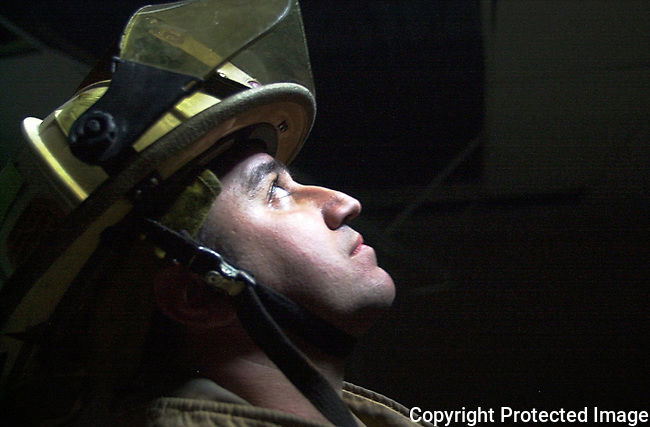 "Captain Gerry Forte, with the Palm Coast, Fla., Fire Department, looks toward an open hole in the floor above him as he awaits ""rescue"" during a training excercise, Tuesday, Jan. 21, 2003.  The department was using the former Palm Coast First Baptist Church building along Palm Coast Parkway as a location for varioius training scenarios prior to its demolition later this week.(Brian Myrick)"