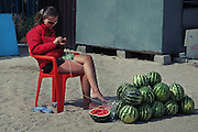 A street vendor selling watermelons waits for customers at the seaside. Ukraine. Azov sea. Fedotov spit. 08.2009. Oksana Yushko for Mare
