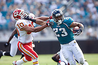 November 08, 2009:     .Jacksonville Jaguars running back Rashad Jennings (23) stiff arms Kansas City Chiefs safety Mike Brown (30) on his way to a touchdown during first half action between the AFC West  Kansas City Chiefs and AFC South Jacksonville Jaguars at Jacksonville Municipal Stadium in Jacksonville, Florida............
