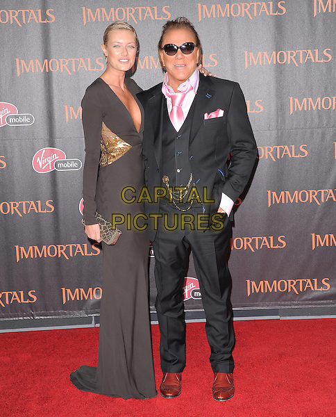 Irson Kudikova & Mickey Rourke.The World Premiere of 'Immortals' held at The Nokia Theater Live in Los Angeles, California, USA..November 7th, 2011.full length brown low cut neckline cleavage gold sequins sequined clutch bag black suit waistcoat pink shirt sunglasses shades couple .CAP/RKE/DVS.©DVS/RockinExposures/Capital Pictures.