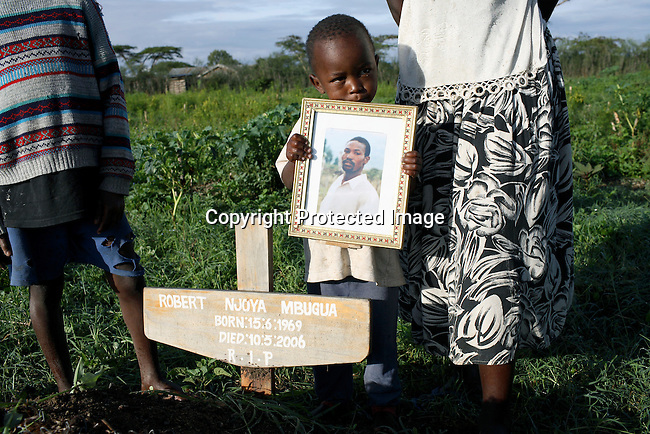 Jack Githuka, age 3, holds the portrait of his late father Robert Njoya as he stands next the grave. His mother and siblings are in the back. Photo: Per-Anders Pettersson. Getty Images
