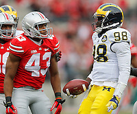Ohio State Buckeyes linebacker Darron Lee (43) stares at Michigan Wolverines quarterback Devin Gardner (98) after sacking him during the first quarter of the NCAA football game against Michigan at Ohio Stadium on Saturday, November 29, 2014. (Columbus Dispatch photo by Jonathan Quilter)