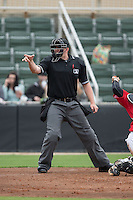 Home plate umpire Jacob Metz makes a strike call during the South Atlantic League game between the Hickory Crawdads and the Kannapolis Intimidators at CMC-Northeast Stadium on April 17, 2015 in Kannapolis, North Carolina.  The Crawdads defeated the Intimidators 9-5 in game one of a double-header.  (Brian Westerholt/Four Seam Images)