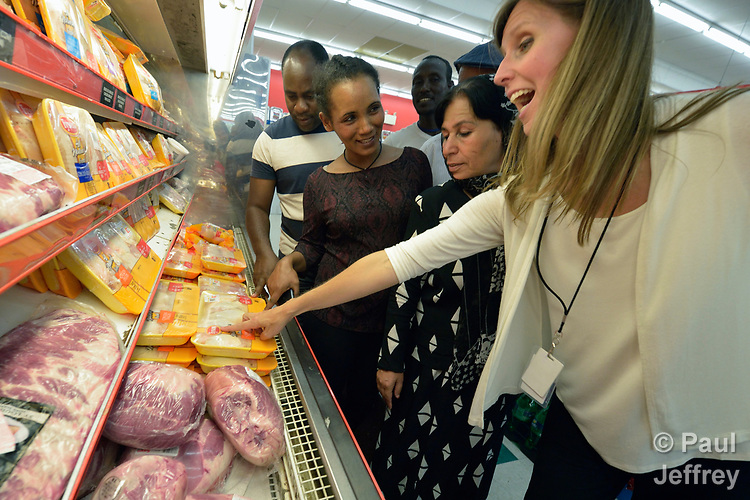 Penny Gushiken (right) leads a cultural orientation class for newly arrived refugees in Lancaster, Pennsylvania. During a visit to a supermarket, participants discuss available food items, including chicken processed in a local plant where many refugees have found employment. The class is sponsored by Church World Service. <br /> <br /> Photo by Paul Jeffrey for Church World Service.
