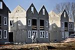 Een bouwvakker met een kruiwagen loopt op een bouwplaats met het kale betoncasco van in aanbouw zijnde eengezinswoningen van een nieuwbouwproject. COPYRIGHT TON BORSBOOM