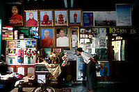 A supporter of U Wirathu, the spiritual leader of the Buddhist nationalist 969 Movement looks at photos of him on the wall of his quarters at the New Maesoeyin Monastery in Mandalay. U Wirathu is an abbot in the New Maesoeyin Monastery where he leads about 60 monks and has influence over more than 2,500 residing there. He travels the country giving sermons to religious and laypeople encouraging Buddhists to shun Muslim business and communities. /Felix Features