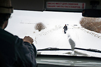 The view through the front window of a car while driving through Kyrgyzstan. A local man walks along a snow covered road.