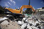 A picture taken on Sep 05, 2013, shows a bulldozer demolishing the home of Shaker Ja'abis in Jabel Mukaber neighborhood southern Jerusalem. Ja'abis decided to demolish his own home to carry out an Israeli court order under the pretext of building without municipality permit. Many Palestinians end up demolishing their homes themselves to avoid the high cost of paying for Israeli government bulldozers, or being sent to prison for not being able to pay. Photo by Saeed Qaq
