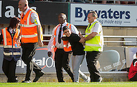 A pitch invaded stops the game as he gestures to Wycombe supporters and is wrestled by stewards during the Sky Bet League 2 match between Leyton Orient and Wycombe Wanderers at the Matchroom Stadium, London, England on 19 September 2015. Photo by Andy Rowland.