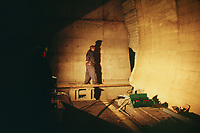 Switzerland. Canton Lucerne. A man controls the armor plate door's closure in the Sonnenberg tunnel in Lucerne during the largest civil defense exercise ever held in the country. A hydraulic cylinder (also called a linear hydraulic motor) is a mechanical actuator that is used to give a unidirectional force through a unidirectional stroke. From 16 to 21 November 1987, almost 1200 men and women converted a motorway tunnel into perhaps the world's largest bunker structure. The civil protectors had to prove during the exercise «Ameise» ( Ants in english) that in an emergency more than 20,000 inhabitants of the city of Lucerne could survive here in the mountain for two weeks. The Sonnenberg Tunnel is a 1,550m  long motorway tunnel, constructed between 1971 and 1976. At its completion it was also the world's largest civilian nuclear fallout shelter, designed to protect 20,000 civilians in the eventuality of war or disaster. Based on a federal law from 1963, Switzerland aims to provide nuclear fallout shelters for the entire population of the country. The construction of a new tunnel near an urban centre was seen as an opportunity to provide shelter space for a large number of people at the same time. The giant bunker was built between 1970 and 1976 at a cost of 40 million Swiss francs. The shelter consisted of the two motorway tunnels (one per direction of travel), each capable of holding 10,000 people in 64 person subdivisions. A seven story cavern between the tunnels contained shelter infrastructure including a command post, an emergency hospital, a radio studio, a telephone centre, prison cells and ventilation machines. The shelter was designed to withstand the blast from a 1 megaton nuclear explosion 1 kilometer away. The blast doors at the tunnel portals are 1.5 meters thick and weigh 350 tons. The logistical problems of maintaining a population of 20,000 in close confines were not thoroughly explored, and testing the installation was difficult because it req