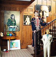 Portrait of interior designer Beth Rudin Dewoody dressed in a kaftan and standing at the bottom of her stairs