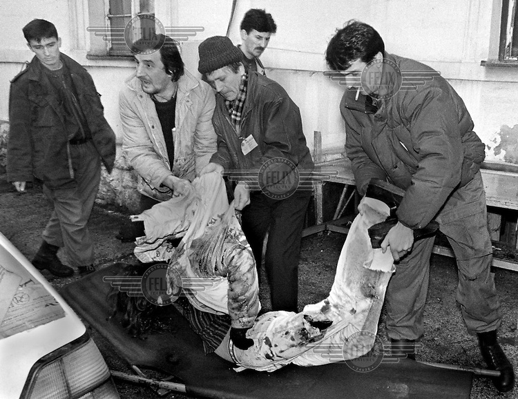 A dead teenage girl is carried into the morgue at Sarajevo's Kosevo hospital on December 6, 1993.