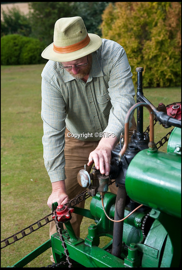 BNPS.co.uk (01202 558833)<br /> Pic: PhilYeomans/BNPS.co.uk<br /> <br /> Lawnmowing history...<br /> <br /> Crank starting the 3 hp motor.<br /> <br /> The worlds first powered mower has taken to the grass once more after an exhaustive restoration by lawnmower nut Andrew Hall from Somerset.<br /> <br /> Forerunner of all the machines that have graced British lawns on sunday afternoons through the decades since, This 1902 Ransome 3hp is a historic survivor from the Edwardian age when chauffers were given the task of grooming their masters lawns and the new fangled machines cost as much as a house.<br /> <br /> The 1 1/4 ton leviathan cost £137 in 1903 - equivalent to a whopping £15,000 in todays money. In consequence they were only available to the very rich, but aristocratic one upmanship lead to a rapid 'lawnmower arms race' untill the first war intervened.