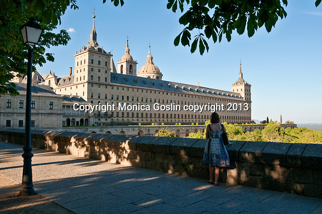 A woman looking at the view of El Escorial at sunset, a historical residence of the kind of Spain and serves as a royal palace, museum, school and monastery that date back to the 16th and 17th centuries