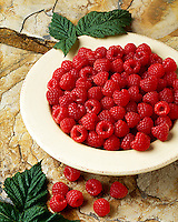 Agriculture - Raspberries in a cream colored stoneware bowl on stone.