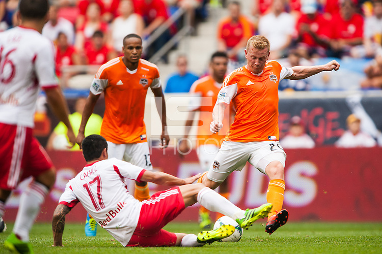 Andrew Driver (20) of the Houston Dynamo shoots as Tim Cahill (17) of the New York Red Bulls goes for a tackle. The New York Red Bulls defeated the Houston Dynamo 2-0 during a Major League Soccer (MLS) match at Red Bull Arena in Harrison, NJ, on June 30, 2013.