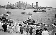 07 May 1969. Passengers aboard the Queen Elizabeth II cruise liner wave to tugboats and excursion boats as they enter New York Harbor during the liner's maiden voyage from Southampton, England to New York City.