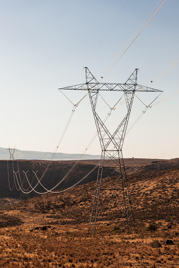 High Voltage transmission towers are sidelit by the sun in a remote part of Southeast Oregon.