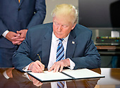 United States President Donald J. Trump signs the first of three Executive Orders concerning financial services at the Department of the Treasury in Washington, DC on April 21, 2017.<br /> Credit: Ron Sachs / Pool via CNP