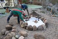 Bau einer Kräuterspirale aus Feldsteinen, Kräuterbeet, Beet, Kräutergarten, Gartenarbeit. Auffüllen mit wasserdurchlässigem Bauschutt