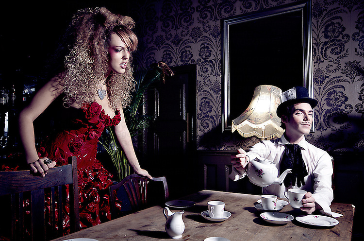 A young woman wearing a red dress looking at a young man sat by a table pouring a cup of tea wearing a top hat.
