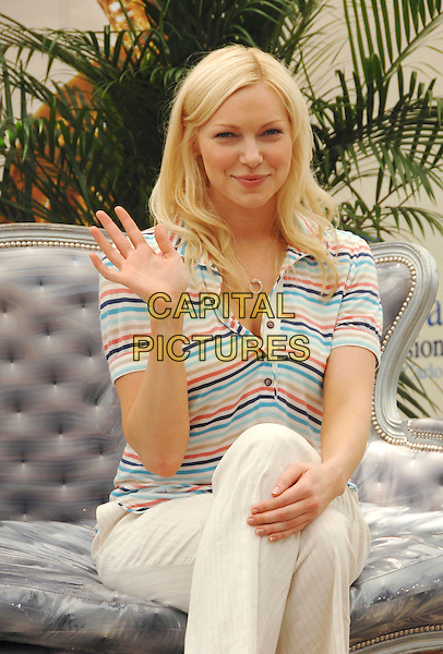 "LAURA PREPON .attends a photocall promoting the television series ""October Road"" on the third day of the 2008 Monte Carlo Television Festival held at Grimaldi Forum in Monte Carlo, Principality of Monaco, .June 10, 2008..half length sitting striped top cream trousers legs crossed hand waving.CAP/TTL .©TTL/Capital Pictures"