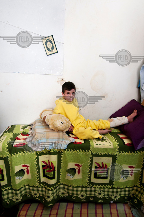 6 year old Kareem, a refugee from Syria, sits on a bed in a room which he shares with 17 other refugees. He has a bandage on his left leg after having been involved in a car accident. /Felix Features
