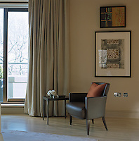 A dark brown leather armchair stands in the corner of the living room