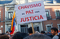 "Demonstrators  supports President Maduro holds a poster entitle ""Chavism is peace with justice""."