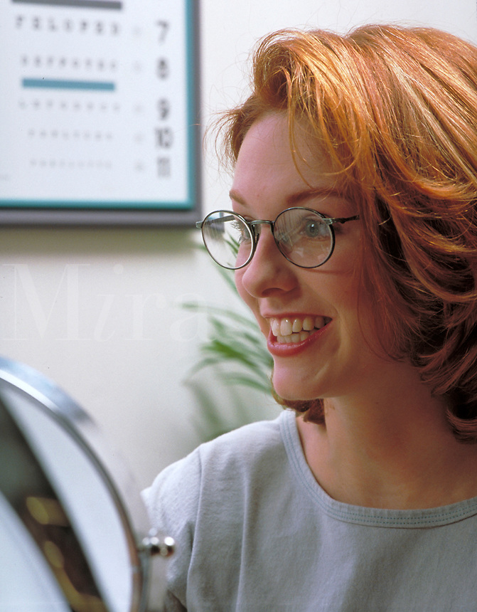 Smiling woman at the optometrist's office trying on new eyeglasses. medical care. H. Bruce, M.R.#H-1.