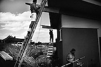 House painters work on the exterior of a house in Great Falls, Montana, USA.