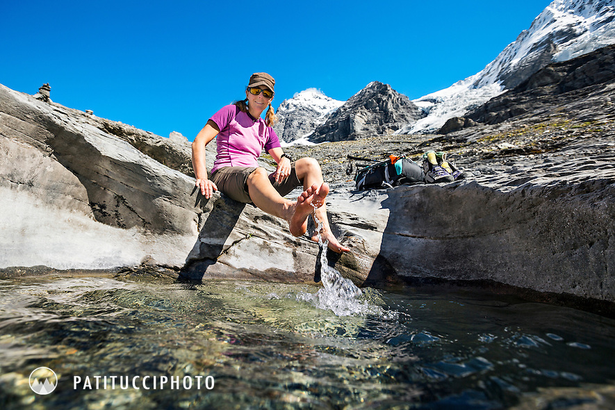 A female hiker stopped at a round pool of water to let her feet cool off while hiking in the Berner Oberland, Switzerland.