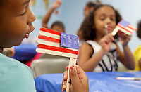 NWA Democrat-Gazette/DAVID GOTTSCHALK  Allison Brooks (left), 8, displays her popsicle stick flag to Brielle Alexander, 7, Monday, July 2, 2018, in the multi purpose room as they participate in the Yvonne Richardson Community Center Summer Camp. Open to students from kindergarten to eighth grade, the eight week long camp offers opportunities to participate in craft projects, water games, indoor activities  and go on field trips.