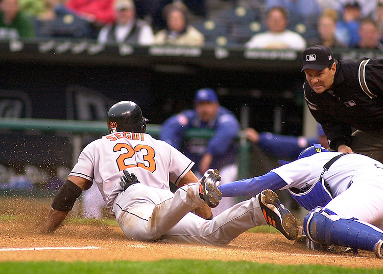 Home plate umpire Mark Barron watches intently as Royals catcher Brent Mayne puts the tag on Baltimore Orioles DH David Segui as he slides safely into home  in the first inning at Kauffman Stadium in Kansas City, Missouri on April 26, 2002.