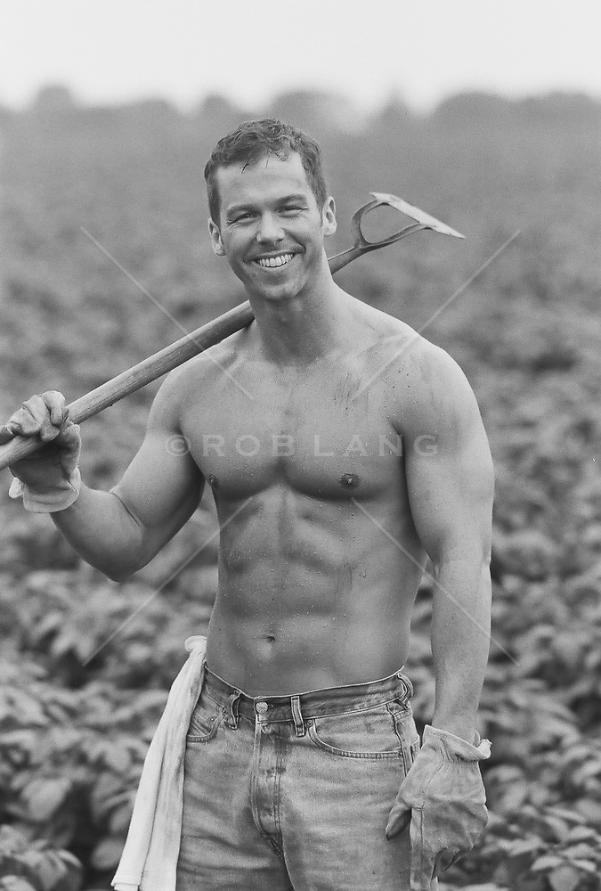 Shirtless Man Holding A Hoe In A Field Rob Lang Images